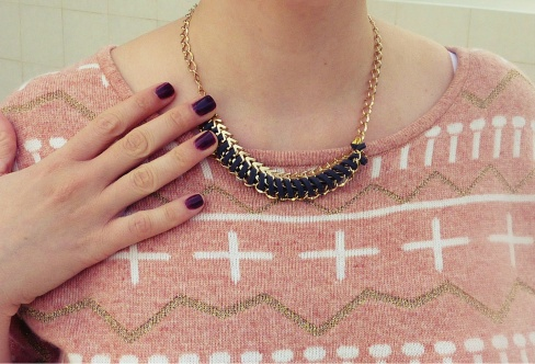 Close up photo of the sweater and a gold and suede necklace
